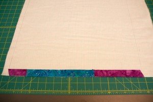 Line up the bottom strip from panel 2 on the bottom edge of your grid fabric, aligning with the line 1-inch from the bottom edge. The strip should be face up with the edge where you marked the line on the left side. Since the edges of the strip are not perpendicular the alignment with the left and right edges will be approximate.